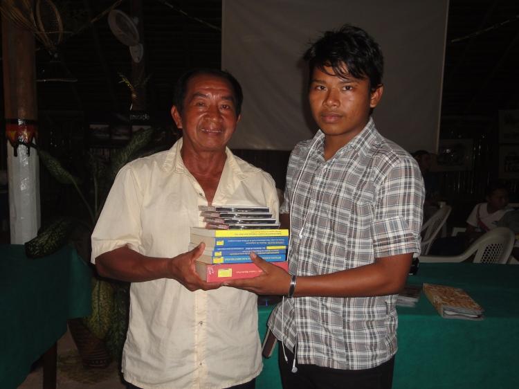 Palestrante Higino Tenório Tuyuka, entrega publicações da FOIRN/ISA ao jovem indígena participante do evento.